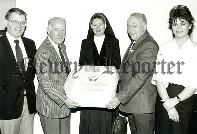 """Mr Pat McAteer (left) President of Newry Credit Union and Mr. Seamus Crossey, Education Officer present to Sister Susan of """"Orana"""" Warrenpoint Road the twenty five pounds weight cake, which was baked by W. D. Irwin, Hill Street, Newry and Portadown and presented to comemorate the 25th Anniversary of the Newry Credit Union. Also in group Mr Joe Hughes, General Manager and Miss Kate McDonnell, member of staff. The cake was used in a guess the weight competition and proceeds presented to Newry Gateway Club."""