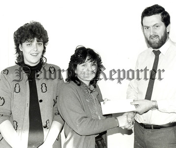 Miss Jennifer Malone, Chairperson of the Newry Concern Group recieves a cheque for £575 from Mr. Eugene Smith, Manager fo the Albion Clothing Co. Edward Street, Newry. The money was raised at the annualsponsored fast at Christmas by the employees and staff. Also in photograph Mrs Ann Havern, Shop Steward. R8904103