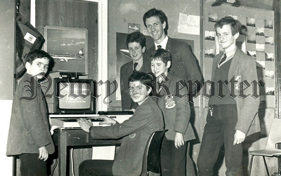 January 1989 - St Louis Grammar school pupils Colin Devlin, Mr Trevor Simpson (teacher), Peter Wachell, Daniel Buckley, Gareth Tierney and Terence Wornock man the school bank at Thursday nights Open Night. R8905101