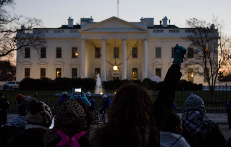 woman raising fist across street from White House, 12/07/14