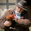 An interpreter and historic farmer makes friends with a chicken at the 1860 Schulz (German) farm.