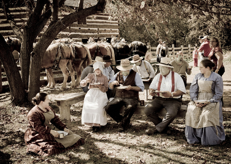 Interpreters and volunteers at the annual Autumn on the Farms event enjoy a classic American farm dinner in the backyard of the Koepsell farmhouse.  Draft horses used for the fall planting are hitched  up behind the farmers waiting to get back to work in the fields.