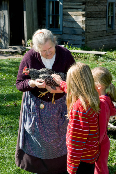 An interpreter  introduces two young visitors to a chicken at the Ketola farm.