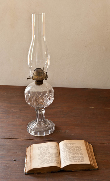 Oil lamp and bible in the bedroom of the Sisel shoe shop in Crossroads village.