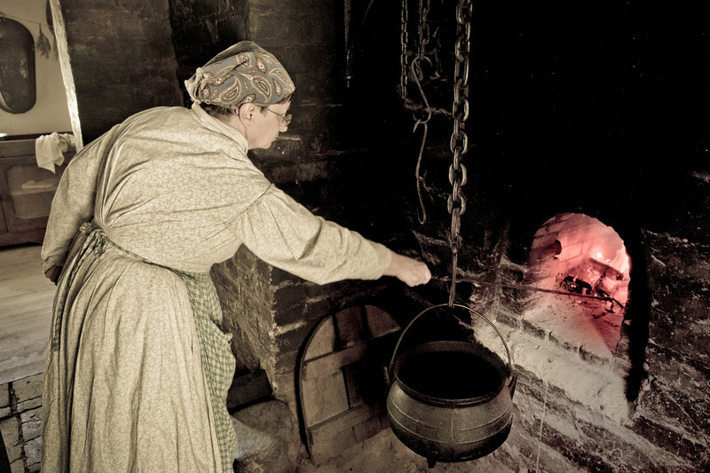 """An interpreter tends a fire in the oven in the """"black kitchen"""" of the 1860 Schulz farmhouse.  The black kitchen was basically a large chimney in the center of the house.  Meat was smoked by hanging it on racks in the chimney.  Bread was baked by first building a fire in the oven.  After the bricks lining the inside of the oven were hot, the coals were removed by dragging them into the pit below the pot seen here.  Many loaves of bread were then placed in the hot oven to bake. Black kitchens fell out of use after a number of years because of the  fire hazard they presented to women in long skirts."""