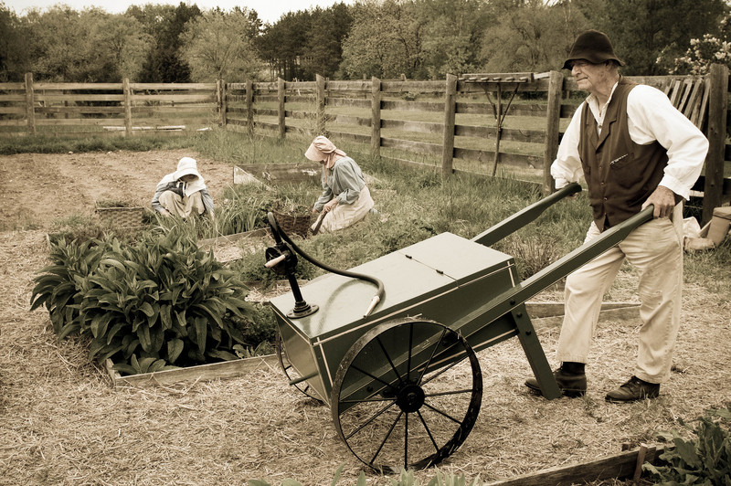 "An interpreter uses his Civil War era ""garden machine"" to water the garden at the Sanford house in Crossroads village."