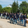 A Civil War reenactors band marches through Crossroads Village to the site of the morning flag raising ceremony at Harmony Town Hall.