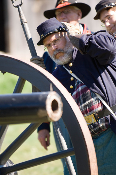An artillery reenactor commander covers his ears before a cannon is fired in Loomer Field in Crossroads Village.