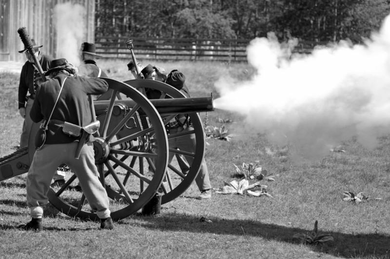 Civil War reenactor artillery men cover their ears while firing a cannon.