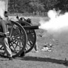 Civil War reenactor artillery men cover their ears while firing a cannon.