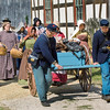 "Union soldiers cart away food and household items they have ""liberated"" from the Schulz farm.  Women from the area, abhorred by this action, follow closely behind."
