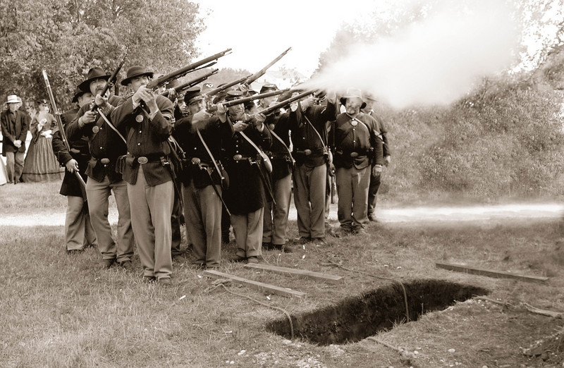 Civil War reenactors give a gun salute at a graveside funeral service in the St. Peter's churchyard.