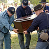Civil War reenactors at a graveside funeral service lower a coffin into a grave in the St. Peter's churchyard.