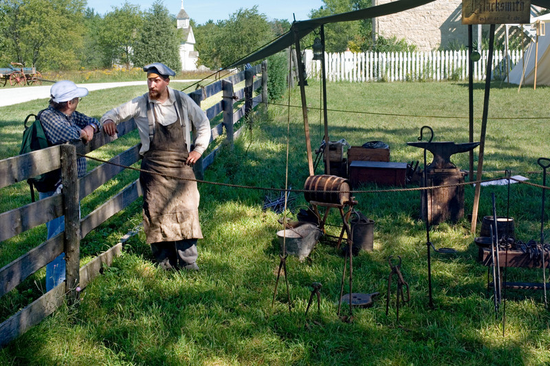 A travelling reenactor blacksmith who follows the Union Army discusses his equipment with a visitor in Crossroads Village.