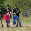 Two young visitors talk to Union soldier reenactors.