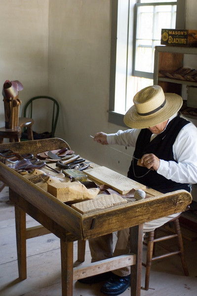A cobbler works at his bench in the Sisal shoe shop