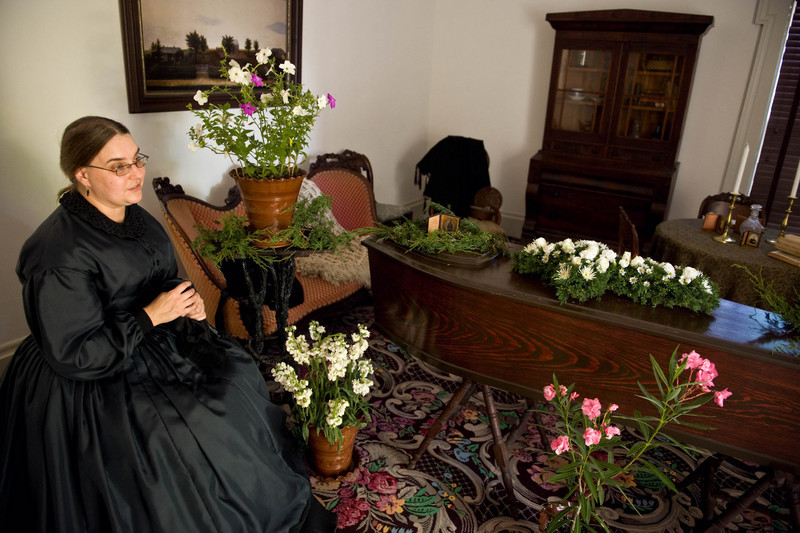 The mother of a deceased Civil War soldier sits by his coffin during a wake in the Sanford house.  Note the small daguerrotype photograph in a metal frame at the head of the coffin, the black draped window and the flowers. Embalming was not practised at the time and  flowers were used  to mask the smell of the body at funerals and wakes.