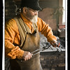 A blacksmith working in the Grotelueschen blacksmith shop in Crossroads village.