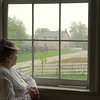 An interpreter lin St. Peter's church looks out the window at the Thomas general store in Crossroads village.