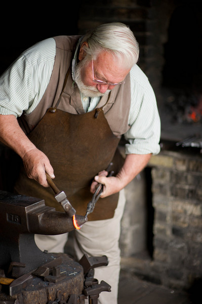 A blacksmith wraps molten metal around the nose of his anvil to make a hook in the Grotelueschen blacksmith shop in Crossroads village..
