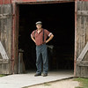 A blacksmith stands at the door to the Grotelueschen blacksmith shop in Crossroads village.