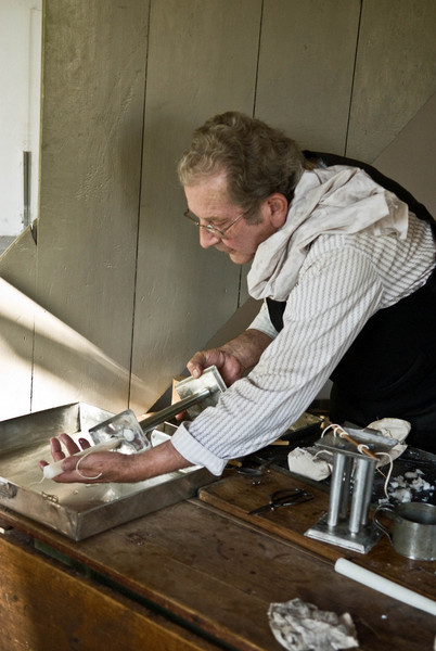 An interpreter demonstrates candle making with molds in the living quarters of the Sisel shoe shop in Crossroads village.