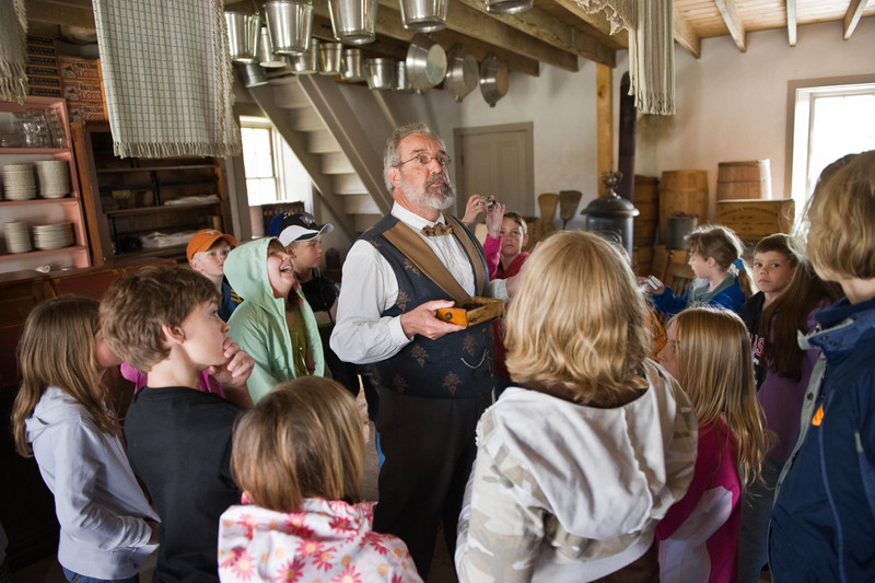An interpreter tells a school group about the Thomas general store in Crossroads village.