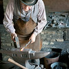 A blacksmith at the Grotelueschen blacksmith shop in Crossroads village shapes a hook on his anvil.