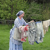 An ineterpreter at the Mary Hafford house in Crossroads village takes down her laundry.