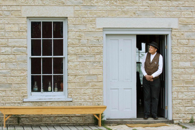 An interpreter working in the Thomas General store in Crossroads village waits at the door for customers.