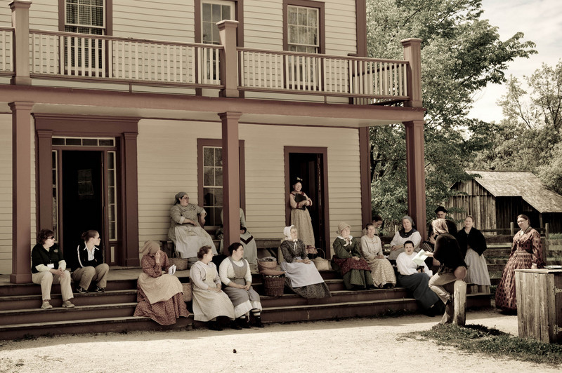Interpreters meet on the porch of the Four Mile Inn in Crossroads village for their daily briefing before the museum opens for the day.