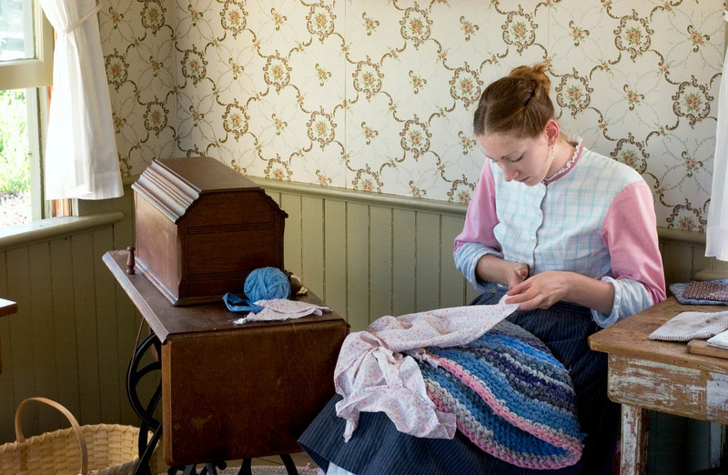 An interpreter in the Mary Hafford house does her mending while waiting for visitors.  Mary Hafford took in both mending and laundry to support her 3 children when she was widowed at an early age.