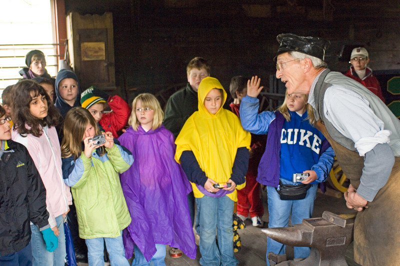 A blacksmith talks to a group of schoolchildren in the Grotelueschen blacksmith shop in Crossroads village.