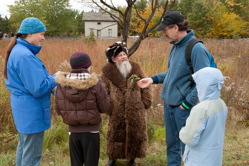 Prairie Bob, dressed in a buffalo skin coat and skunk skin hat, is a well known expert on Wisconsin native prairies.  Standing in front of the Mary Hafford house in Crossroads Village he chats with visitors as they enter the museum.