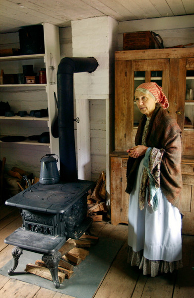 An interpreter talks to a visitor in the kitchen of the 1890 Pedersen farmhouse.  When Old World Wisconsin first opened in 1976 the Queen of Denmark came to dedicate this farm.