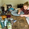 An interpreter works on a braided rug on the kitchen table of the 1890 Pedersen farmhouse.  When Old World Wisconsin first opened in 1976 the Queen of Denmark came to dedicate this farm.