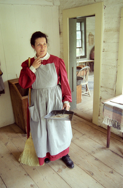 An interpreter pauses while sweeping the floor at the 1890 Pedersen farmhouse.  This view is looking from the living room into the kitchen area.  When Old World Wisconsin first opened in 1976 the Queen of Denmark came to dedicate this farm.