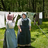 Two interpreters stop to chat after hanging their laundry out to dry on a beautiful spring day at the Ketola farm.  Note the prolific dandelions at Ketola.