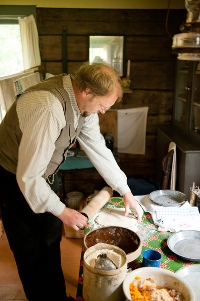 An interpreter makes a pie in the kitchen of the 1915 Ketola (Finnish) farmhouse.