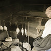 An interpreter cooks fish over a fire in the sauna at the Finnish Ketola farm.