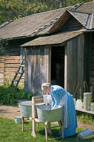 An interpreter washes clothes the hard way at the 1915 Ketola (Finnish) dairy farm.  Note the milk bottles on the bench.
