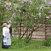 An interpreter pauses to smell the lilacs at the 1915 Ketola (Finnish) farm.