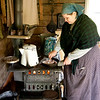 An interpreter cooks sausages for breakfast in the kitchen of the 1915 Ketola (Finnish) farmhouse.