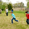 Schoolchildren learning to play with hoops and sticks at the Sanford farm in Crossroads Village.
