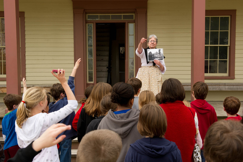 An interpreter on the porch of the Four Mile Inn in Crossroads Village talks to schoolchildren about life in the 19th century.