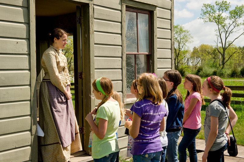 An interpreter at the Mary Hafford house in Crossroads village tells schoolchildren about the hard life that Mary Hafford had after her husband was killed.