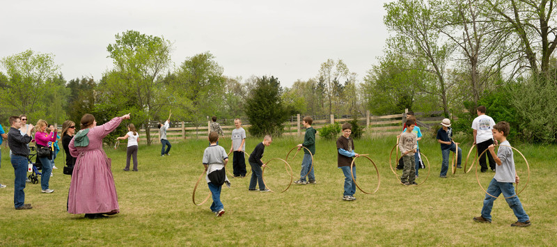 Schoolchildren playing with hoops and sticks at Sanford farm.