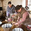 Interpreters in the summer kitchen at the Schottler farm grind pork to be used in sausages.