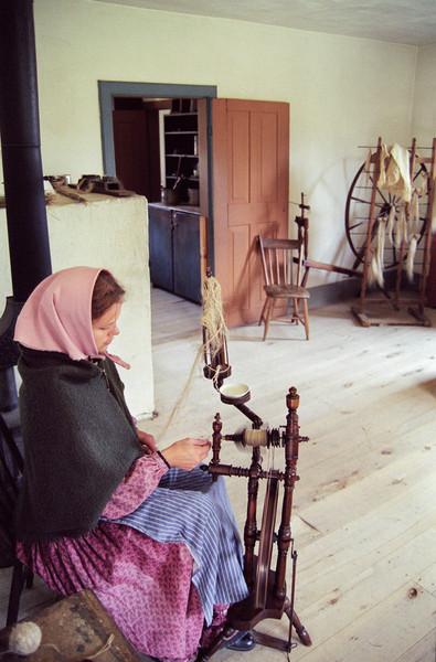 An interpreter spins flax in the Schulz farmhouse.