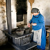 An interpreter boils potatoes in the summer kitchen at the Schottler farm.  Note the blackened wall to her right caused by escaping smoke from the brick oven.
